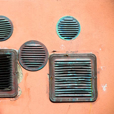 Detail of an old copper ventilation grids in a colored plastered wall
