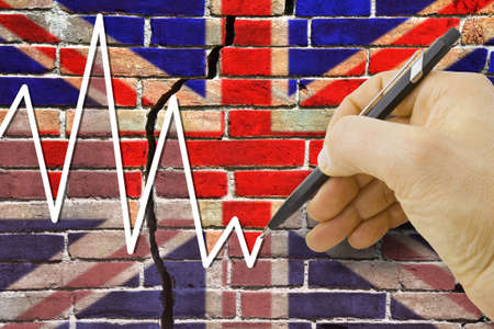 Hand drawing a graph about the performance of the English economy against a cracked brick wall with British flag - concept image