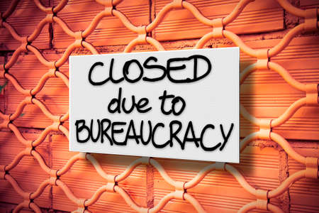Closed due to bureaucracy - concept image with a warning sign against a closed metal shutter