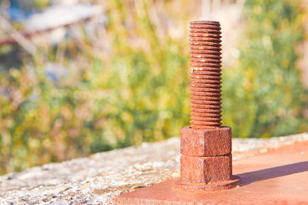 Old rusty anchor bolt with iron plate - image with copy space