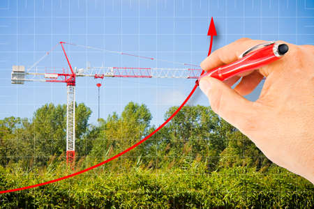 Hand draws a growing chart about building activity against a background with a tower crane in a construction site surrounded by nature - concept image