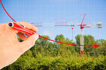 Hand draws a decreasing chart about building activity against a background with a tower crane in a construction site surrounded by nature - concept image