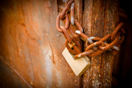 Rusty metal gate closed with padlock - concept image with copy space