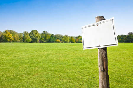 Wooden blank sign indicating against a green mowed lawn with trees and sky on background in the countryside - image with copy space Фото со стока