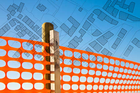Construction site with safety orange grid against a cadastral map - concept image