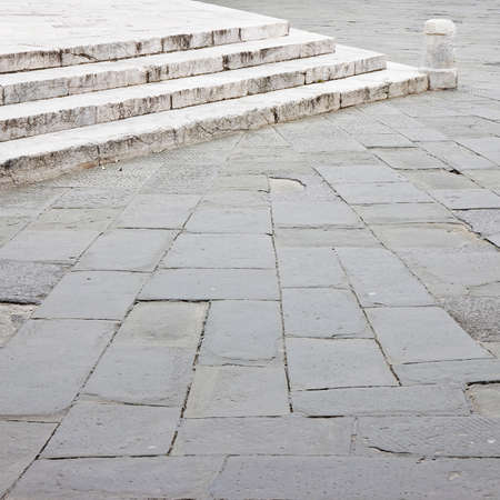 Old medieval stone pavement and marble staircase