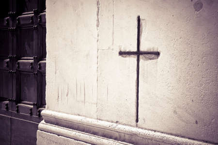 Iron Christian cross snuggled against a white stone on a italian facade church - image with copy space