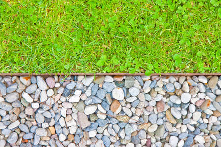 White gravel floor and fresh green lawn with clovers and rusty metal containment profiles.