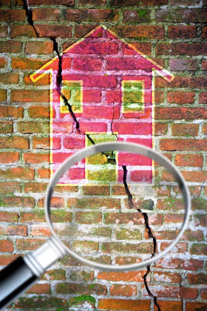 Brick wall with a large crack with a colored house drawn on it - concept image seen through a magnifying glass - image with copy space