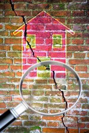 Pared de ladrillo con una gran grieta con una casa de color dibujada en ella - imagen conceptual vista a través de una lupa - imagen con espacio de copia