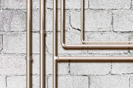 Water and gas metal pipeline in front of a concrete wall. Reklamní fotografie