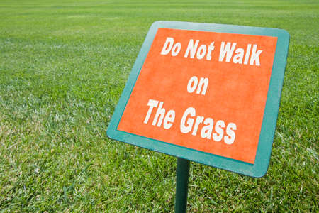 Do not walk on the grass - concept image white text on signboard and fresh green lawn.
