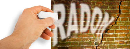 Hand removes radon gas from a cracked brick wall with radon gas escaping - concept image with copy space