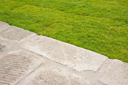 Old paving made with stone blocks in a pedestrian zone and fresh green lawn. Imagens