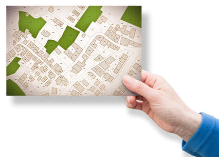 Imaginary cadastral map of territory with buildings, roads, land parcel and free green land available for building construction. Concept image with a female hand holding an postcard. 스톡 콘텐츠