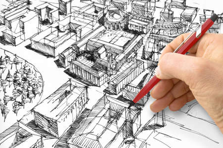 Planning a new city - Engineer-architect drawing with a pencil a sketch of a new modern imaginary town - concept image. Banque d'images