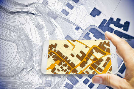 Hand holding a smartphone with an imaginary cadastral map of territory with buildings, roads and land parcel - 3D rendering  写真素材