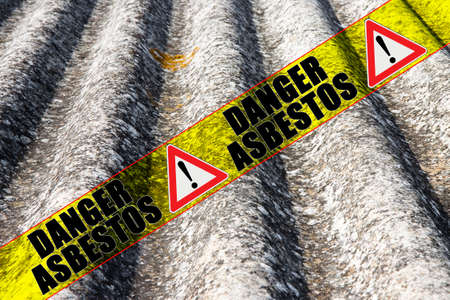 "The message ""danger asbestos"" written on a yellow stripe"
