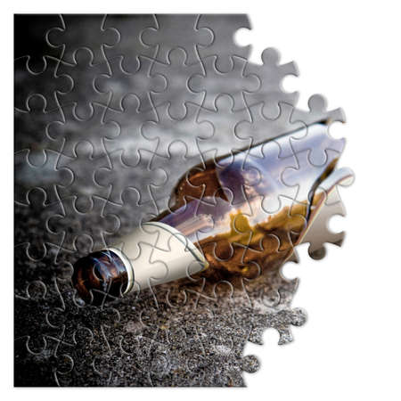 Broken bottle of beer resting on the ground - Free themselves from alcohol addiction - concept image in jigsaw puzzle shape 스톡 콘텐츠