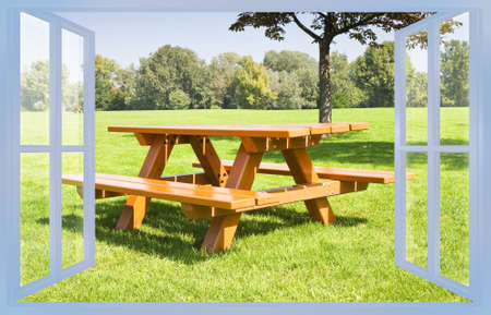Wooden new picnic table on a green meadow of a public park with trees on background - concept image. Фото со стока