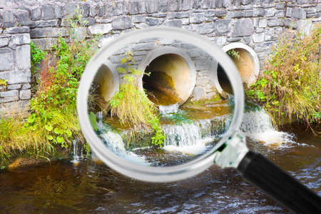 Toxic water running in concrete drainpipe towards the river - Concept image seen through a magnifying glass.
