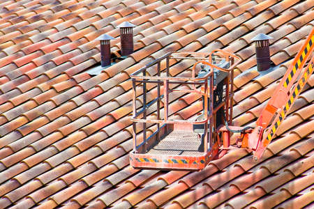 Aerial platform for repairing a roof with clay tiles and shingles. Stock Photo
