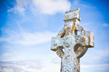 Celtic carved stone cross against a sky background - image with copy space