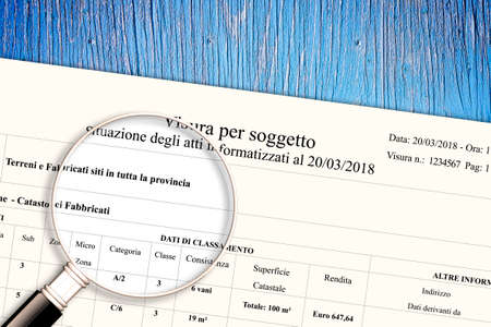 Imaginary italian cadastral document with cadastral information for land and buildings property - concept image with magnifying glass specific for the italian market - texts are not subject to copyright and numbers are totally invented.