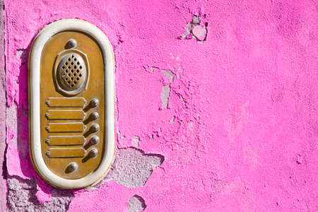 Old stone and brass bell system against a colored plaster wall - image with copy space.
