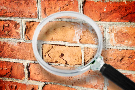Old italian brick wall with damaged bricks - Concept image seen through a magnifying glass.