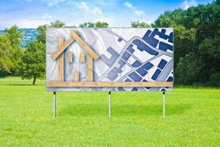 Blank advertising billboard in a green field with wooden building - The advantages of wood as a building material in the construction industry - concept image. Imagens