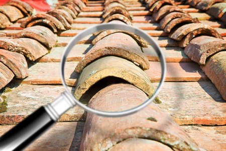 Search for water infiltration on old roof - concept image with magnifying glass