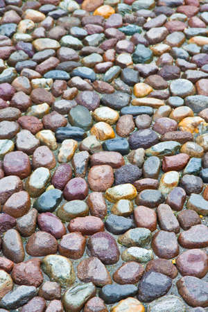 Detail of a coloful rounded pebble floor, permeable to water, with polished stone in a italian square.