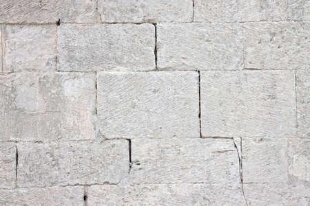 Deep crack in old medieval stone wall made of big blocks. Reklamní fotografie