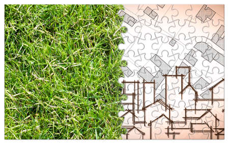 From nature to a new city - jigsaw puzzle concept with a green grass area and an imaginary city map with buildings and roads - nature becomes a city. Reklamní fotografie
