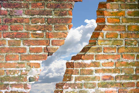 Through a crack of a brick wall you see the sky - escaping concept image.