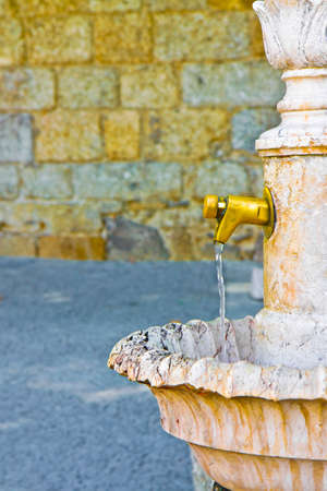 Water flowing from an old portuguese brass fountain and marble with floral shapes. Archivio Fotografico