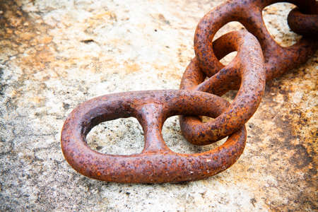 Detail of an old rusty metal chain anchored to a concrete block