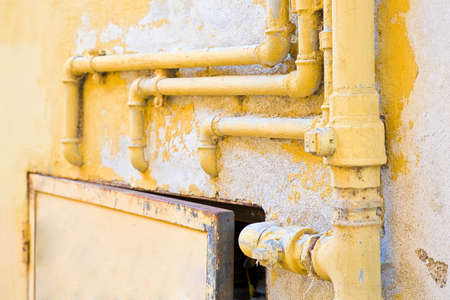 Old domestic protective metal box of water and methane gas against a damaged varnished plaster wall with metal pipeline fixed with brackets on it.