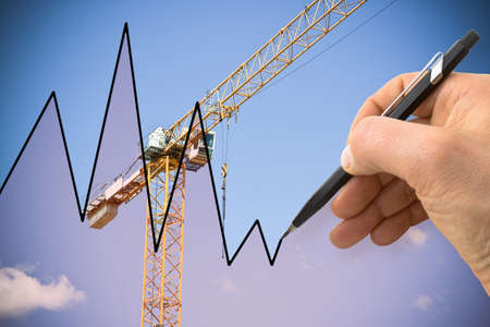 Hand draws a graph with a background of a construction site - concept image
