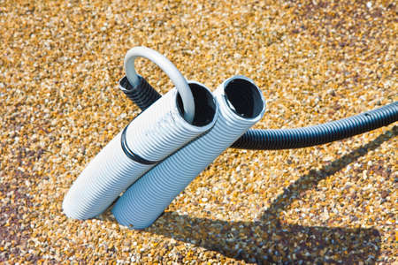Corrugated plastic pipe for electric cable coming out from a gravel ground Foto de archivo