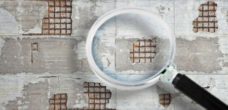 Old reinforced concrete structure with damaged and rusty metallic reinforcement - concept image seen through a magnifying glass.