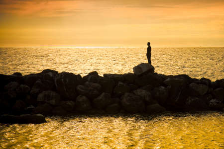 The man and the sea into the sunset - concept image - silhouette style background