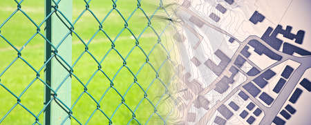 Fencing off private properties - concept image with a green metal wire mesh against a green area and an imaginary city map.