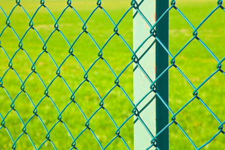Green metal wire mesh against a green area of a public park or private property.