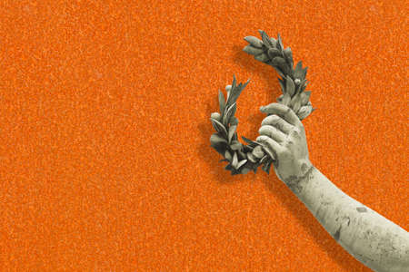 Hand holds a laurel wreath - concept image against a rusty metal background - Success and fame concept image with copy space.