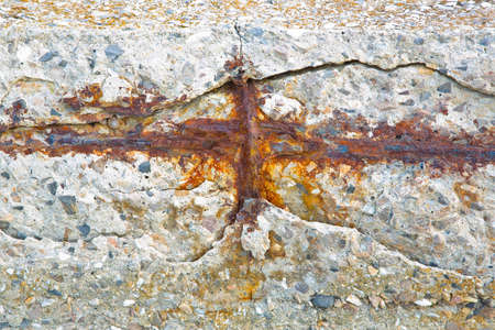 Old reinforced cracked concrete structure with damaged with rusty metallic reinforcement bars.