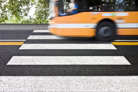 Black and white pedestrian crossing with bus on background - Notes: the silhouette of the car has been modified and is not recognizable.