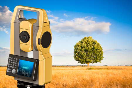 Isolated oak tree in a golden wheat field and 3D rendering of a geodesic device, called Total Station used for the survey of topographic maps and topographical survey. Reklamní fotografie