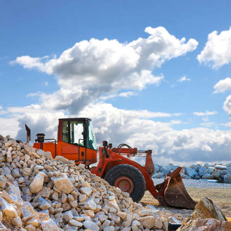 A digger builds a dam of white stones on a construction site